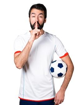 Jogador de futebol segurando uma bola de futebol fazendo um gesto de silêncio