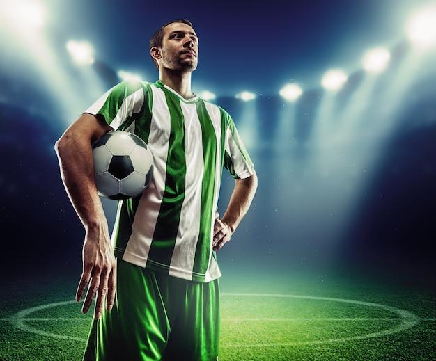 Jogador de futebol segurando uma bola no campo de futebol à noite