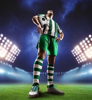 Jogador de futebol segurando uma bola no campo de futebol