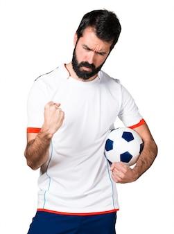 Jogador de futebol sortudo segurando uma bola de futebol