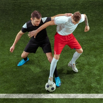 Jogador de futebol tentando pegar a bola na grama verde