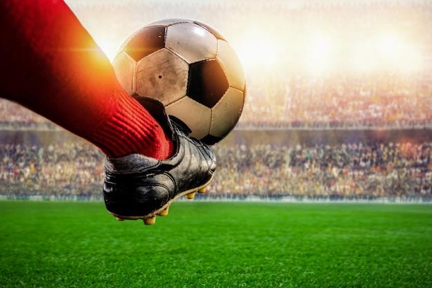 Jogador de futebol vermelho chutando a bola no estádio