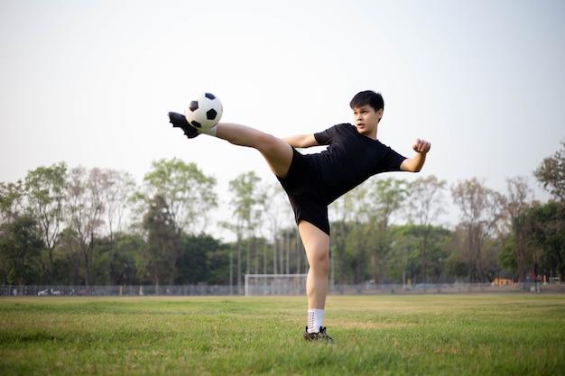 Jogador de futebol vestindo camiseta preta e calça praticando chutando a bola