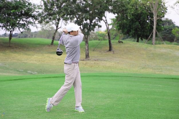 Jogador de golfe asiático teeing fora da bola de golfe da caixa de tee