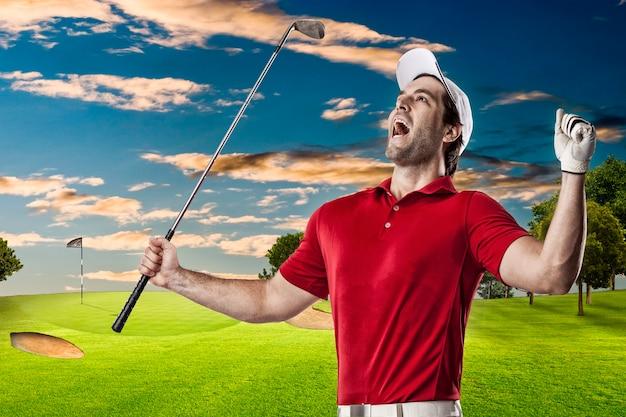 Jogador de golfe com camisa vermelha comemorando, em um campo de golfe.