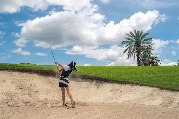 Jogador de golfe feminino jogando areia atirou no campo de golfe profissional