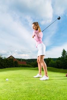 Jogador de golfe feminino jovem em curso fazendo balanço do golfe