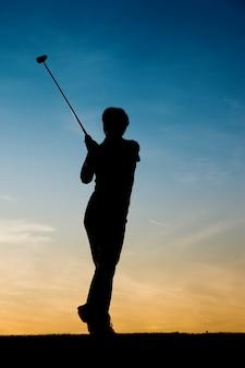 Jogador de golfe feminino sênior ao pôr do sol