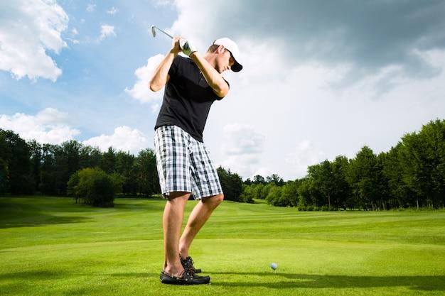 Jogador de golfe jovem em curso, fazendo o balanço do golfe