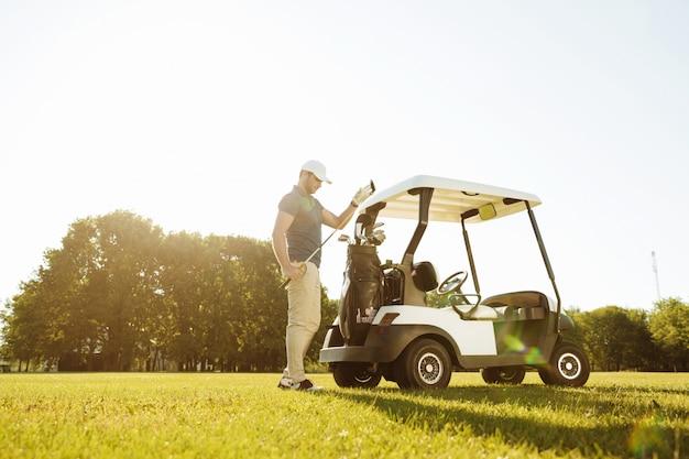 Jogador de golfe levando tacos de um saco em um carrinho de golfe