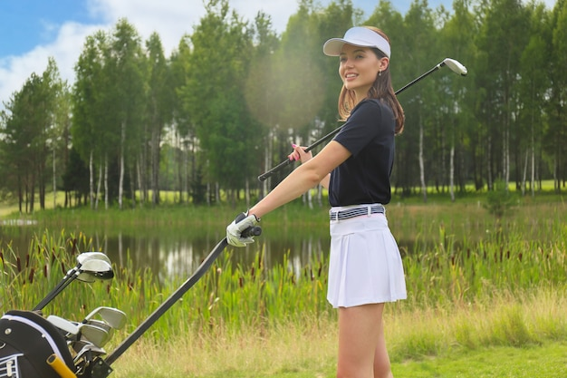 Jogador de golfe linda mulher carregando uma bolsa de golfe e sorrindo.