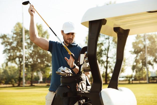 Jogador de golfe masculino considerável que leva clubes de um saco em um carrinho de golfe