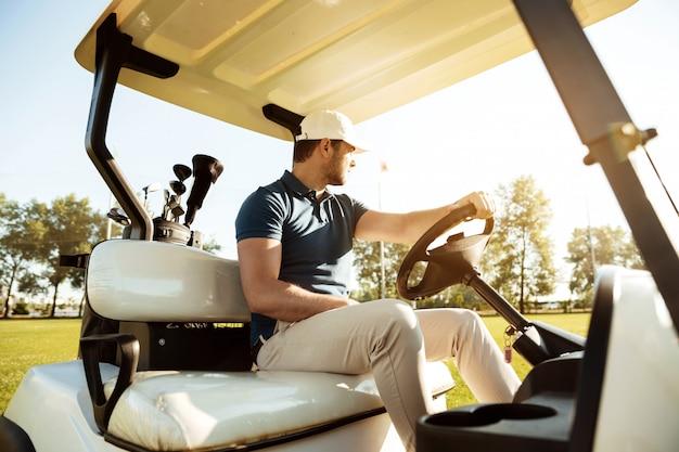Jogador de golfe masculino dirigindo um carrinho com saco de tacos de golfe