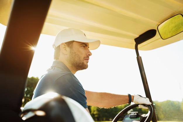 Jogador de golfe masculino dirigindo um carrinho de golfe