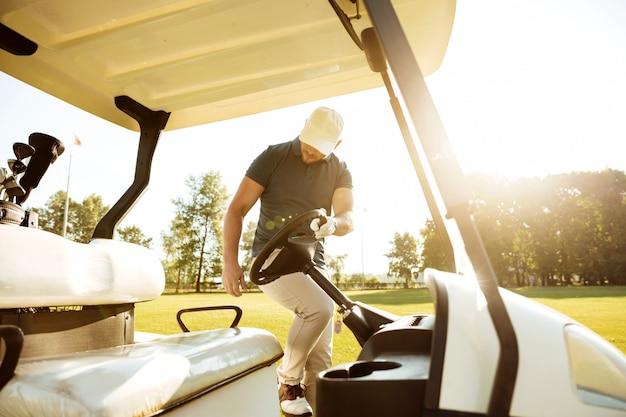 Jogador de golfe masculino, ficando em um carrinho de golfe