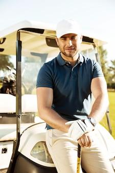 Jogador de golfe masculino novo considerável com clube que descansa