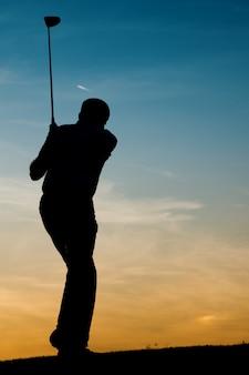 Jogador de golfe masculino sênior ao pôr do sol
