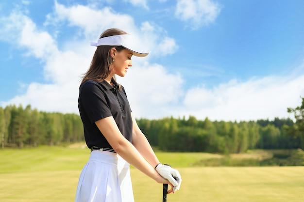 Jogador de golfe mulher acerta um tiro de campo em direção à casa do clube.