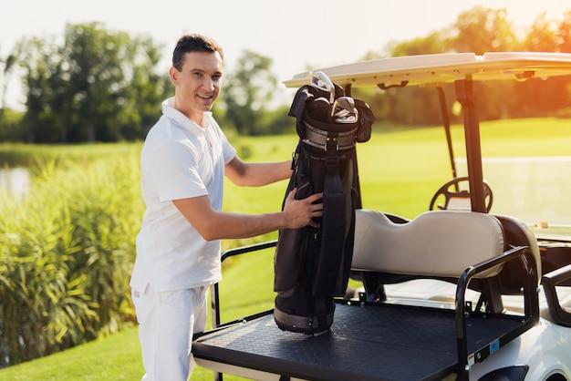 Jogador de golfe orgulhoso perto do passatempo caro do carro com erros.