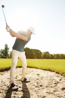 Jogador de golfe prestes a bater a bola em um bunker de areia