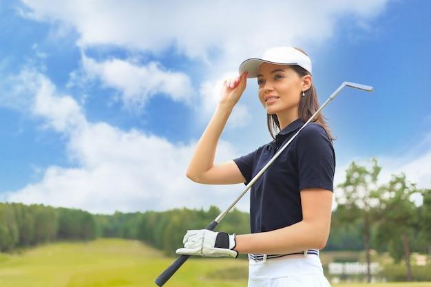 Jogador de golfe profissional feminino segurando o clube de golfe no campo e desviar o olhar. jovem mulher de pé no campo de golfe em um dia ensolarado.
