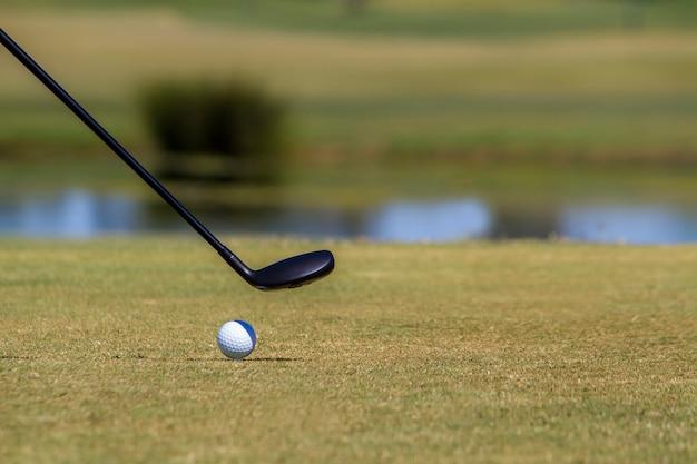 Jogador de golfe que bate uma bola de golfe em um campo de golfe bonito.