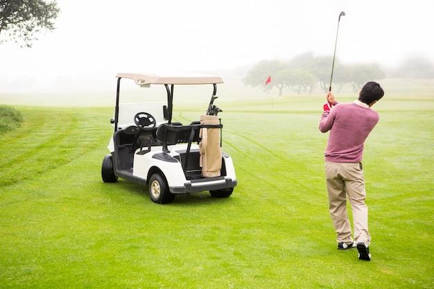 Jogador de golfe que sai ao lado de seu carrinho de golfe