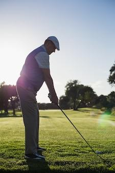 Jogador de golfe que teeing fora para o dia