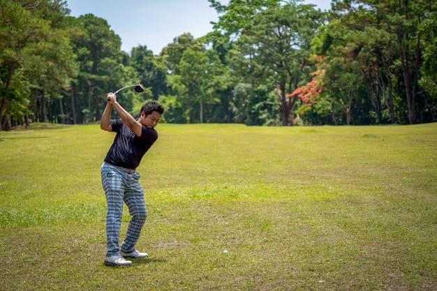Jogador de golfe swing bola de golfe no fairway para buraco na bela floresta verde