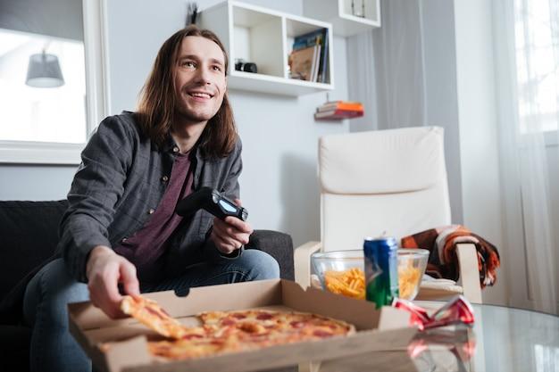 Jogador de homem sorridente, sentado em casa dentro de casa e jogar jogos