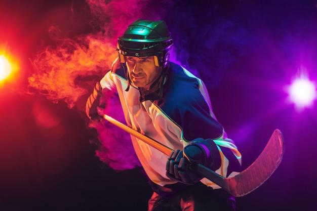 Jogador de hóquei com o taco na quadra de gelo e fundo de cor néon escuro