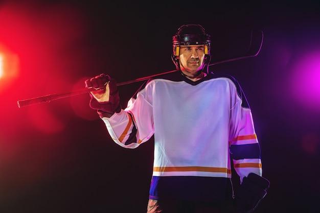 Jogador de hóquei com o taco na quadra de gelo e parede de néon escuro