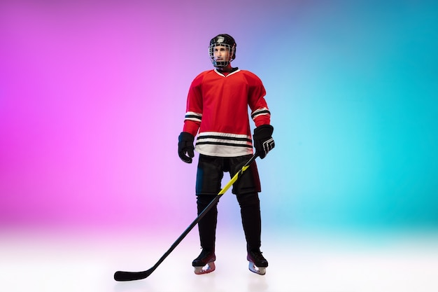 Jogador de hóquei com o taco posando na quadra de gelo e uma parede gradiente de cor neon