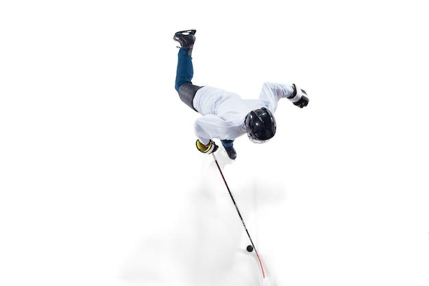 Jogador de hóquei masculino irreconhecível com o taco na quadra de gelo e fundo branco. desportista usando equipamento e praticando capacete. conceito de esporte, estilo de vida saudável, movimento, ação. vista do topo.