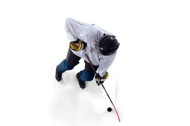 Jogador de hóquei masculino irreconhecível com o taco na quadra de gelo e fundo branco
