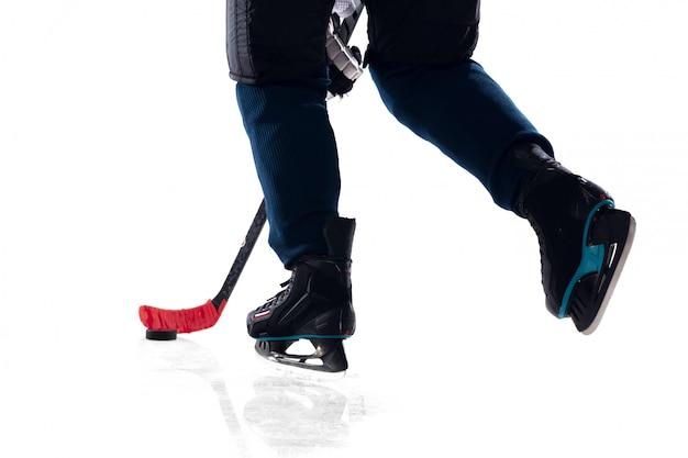 Jogador de hóquei masculino irreconhecível com o taco na quadra de gelo