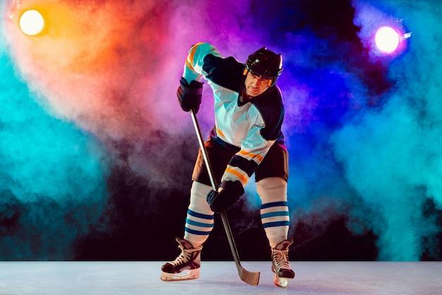 Jogador de hóquei masculino líder na quadra de gelo e fundo colorido de néon escuro