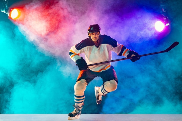Jogador de hóquei masculino líder na quadra de gelo e fundo de cor neon escuro com lanternas