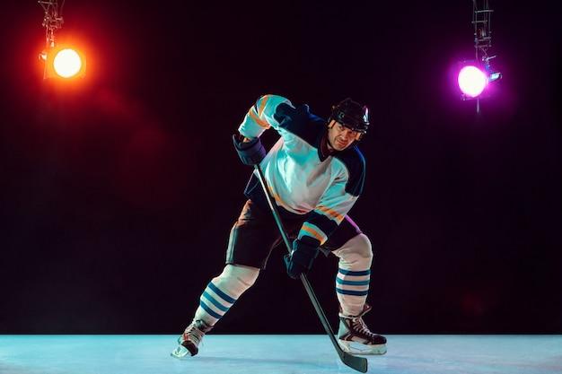 Jogador de hóquei masculino na quadra de gelo e fundo de néon escuro, esporte