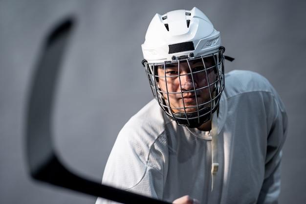 Jogador de hóquei no gelo profissional sentir-se irritado, uma iluminação no quarto escuro.
