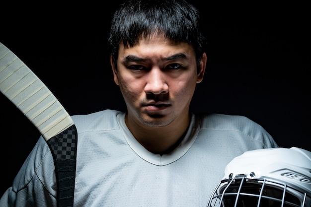 Jogador de hóquei no gelo profissional sinta-se irritado, uma iluminação no quarto escuro.