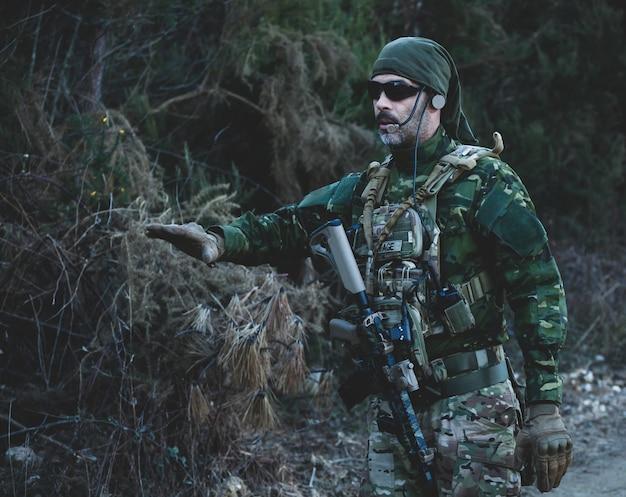 Jogador de jogo militar de airsoft em uniforme de camuflagem e rifle de assalto armado.