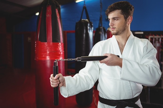 Jogador de karatê praticando com nunchaku