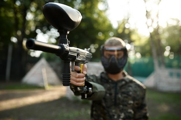 Jogador de paintball aimimg com arma no playground. esporte radical com arma pneumática e balas ou marcadores de tinta, jogo militar ao ar livre, táticas de combate