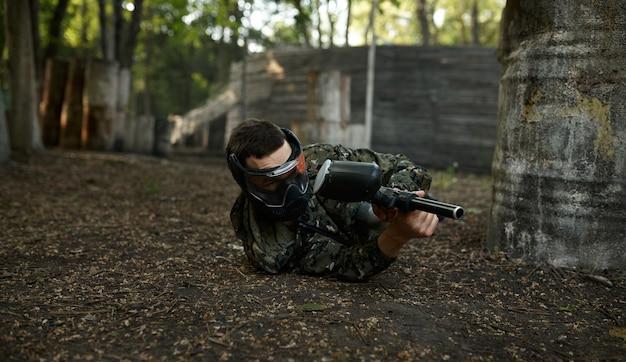 Jogador de paintball masculino com arma de fogo atira deitado no chão, parque infantil na floresta no fundo. esporte radical com arma pneumática e balas ou marcadores de tinta, jogo de equipe militar ao ar livre