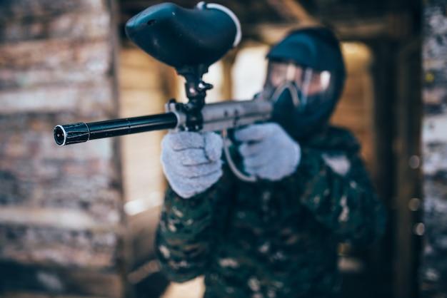 Jogador de paintball masculino com arma marcador nas mãos, vista frontal, foco na arma, batalha de inverno. jogo de esporte radical, soldado luta com máscara de proteção e uniforme