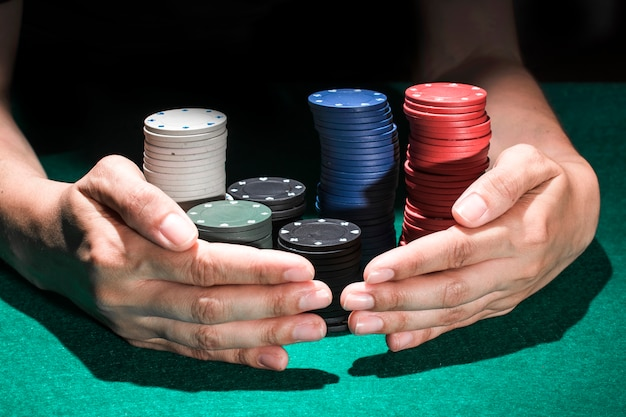 Jogador de poker, ajuntando uma grande pilha de fichas
