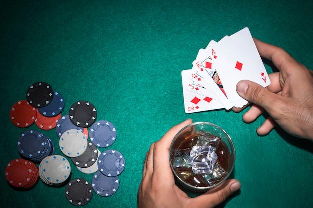 Jogador de pôquer com copo de uísque e royal flush cartão na mesa de poker