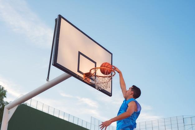 Jogador de rua de basquete fazendo um slam dunk