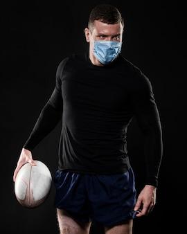 Jogador de rúgbi com máscara médica segurando uma bola